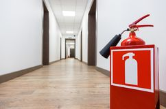 Fire extinguisher in empty business center corridor stock image