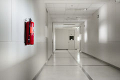 Fire extinguisher. In empty white corridor royalty free stock photography