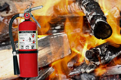 Fire extinguisher with a fire background stock image