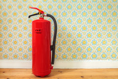 Fire extinguisher in front of retro flower wallpaper. Fire extinguisher on an old wooden floor in front of retro flower wallpaper royalty free stock images