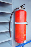 Fire extinguisher on the grey wall. Red fire extinguisher on the grey wall Stock Photos