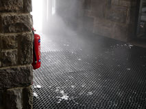 Fire extinguisher. Hang on the wall, cloud of mist look like smoke, comes through the door royalty free stock images