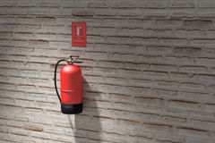 Fire extinguisher hanging on brick wall Stock Image