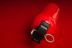 Fire extinguisher lying on a red surface Royalty Free Stock Photography
