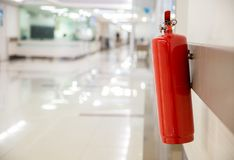 Fire extinguisher in the operating department . Install a fire extinguisher on the wall in building. Dry chemical powder fire exti. Nguisher in corridor .a red stock images