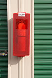 Fire extinguisher on the side of a metal building Stock Images