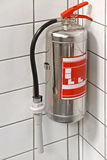 Fire extinguisher. Silver fire extinguisher in building corner Royalty Free Stock Photography