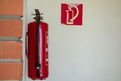 The fire extinguisher is suspended on the wall. The fire extinguisher is suspended on the white wall royalty free stock images