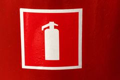 Fire extinguisher symbol on red wall close stock image