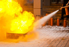 Fire Extinguisher Training. A fire extinguisher is used to put out a training fire royalty free stock images