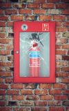 Fire extinguisher in wall box with cracked glass. brick wall Stock Photos