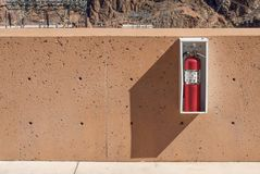 Fire extinguisher on the wall. In desert dry environment royalty free stock images
