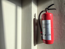 Fire extinguisher on the wall. Fire extinguisher on the wall in a morning light Stock Images