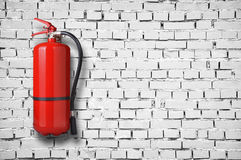 Fire extinguisher. On white brick wall stock photo