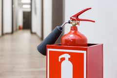 Fire extinguisher in white corridor of business center stock image