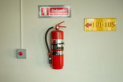 Fire extinguisher on the white wall. Fire extinguisher on the white wall with alarm button Stock Photos