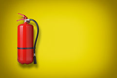 Fire extinguisher. On the yellow wall Royalty Free Stock Images