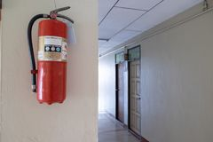 Fire extinguishers are installed on the walls along the corridor in the building to be used for fire. The fire extinguishers are installed on the walls along the royalty free stock photography