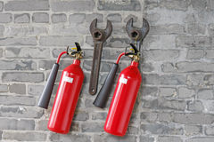 Fire extinguishers and spanners hanged on brick wall Stock Photography