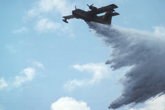 Fire extinguishing. A plane pouring tons of water on a bush fire in summer stock image