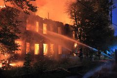 Fire extinguishing. Firefighters  extinguishing a fire in the dark with streams of water Stock Photos