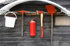 Fire extinguishing tools. Hanging on wooden wall royalty free stock image