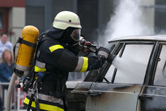 Fire fight against burning car. A fire-fighter works at a burning car stock photos