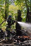 Fire fighter. Fireman with hose extinguishing a fire in ruins Royalty Free Stock Image