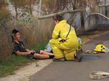 Fire fighter attend to a peer without uniform during a bush fire in an suburban area of Knox City in Melbourne east. Melbourne, Australia - April 13, 2018: Fire Royalty Free Stock Photos