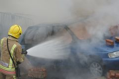 Fire fighter, car fire Royalty Free Stock Image