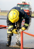 Fire fighter conecting hose Royalty Free Stock Photos