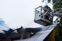 Fire fighter extinguishing flames on burning roof stock photos