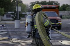 Fire fighter getting fire hose off rig. Fire fighter deploying fire hose off the fire truck stock image