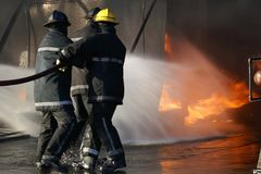 Fire fighter going into smoke filled building stock photo