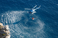 Fire fighter helicopter collect water over the sea. Blue helicopter flies over the blue water, and uses orange basket to carry water royalty free stock photo