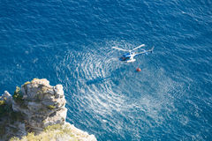 Fire fighter helicopter collect water over the sea. Blue helicopter flies over the blue water, and uses orange basket to carry water royalty free stock photography
