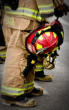 Fire fighter holding helmet. A fire fighter in uniform holds a helmet