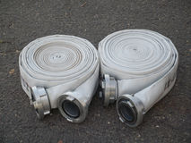 Fire fighter hose on the asphalt background. Two fire fighter hose in outdoor Stock Image