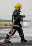 Fire-fighter with hose stock photo