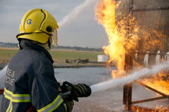 Fire fighter with hose Stock Photos