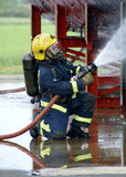 Fire-fighter with hose Stock Images