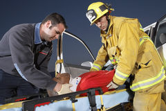Fire Fighter And Paramedic Assisting Man At Crash Site Royalty Free Stock Photography
