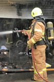 Fire fighter spraying water on a garage on fire in rain Royalty Free Stock Photo