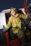 Fire Fighter Standing At Fire Brigade's Door. Alert mature fire fighter standing at fire brigade's door Stock Image