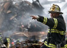 Fire Fighter Wearing Black and Yellow Uniform Pointing for Something Stock Photography