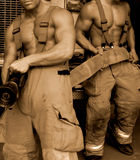 Fire fighters. Male fire fighters in sepia Royalty Free Stock Photos