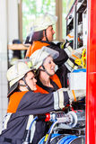 Fire fighters attaching hose at hose laying vehicle Stock Image