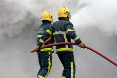 Fire fighters fighting fire with hose Royalty Free Stock Photo