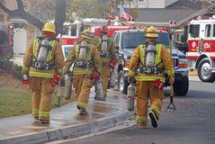 Fire Fighters Heading to a Fire. Fire fighters carrying their tools and equipment head to a house on fire Stock Photography