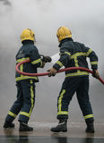 Fire-fighters with hose Stock Photos